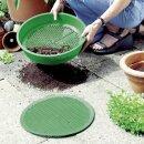 Erde die durch das grüne Gartensieb gesiebt wird.